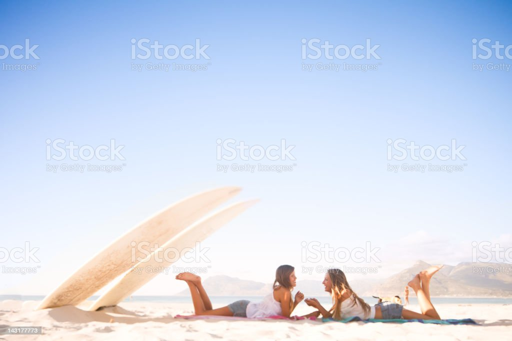 Two attractive young women laughing and chatting on the beach royalty-free stock photo