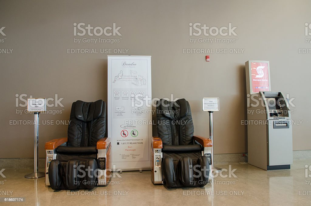 Two automatic massage chairs with a banking machine stock photo