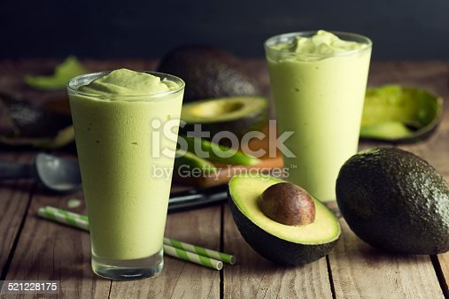 A freshly made avocado shake, or smoothie, in glasses on a wooden table. Avocados, a knife, a cutting board and an ice cream scoop are in the background. Avocado shakes originated in southeast Asia and are also found in Brazil, but are becoming popular across the globe.