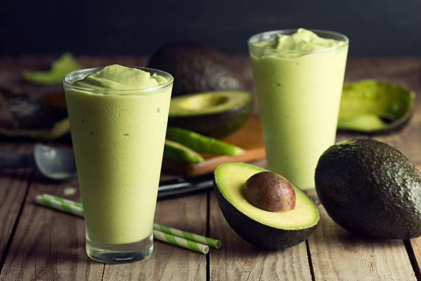 Two Avocado Shakes or Smoothies with Ingredients stock photo