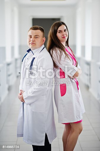 istock Two awesome doctors or medical workers wearing white coats pose with stethoscope in clinique or hospital. 814965724