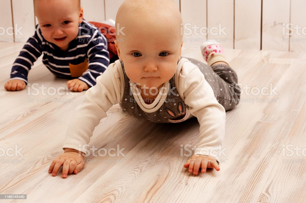 Two babies crawling on the floor, a boy and a girl. The boy is...