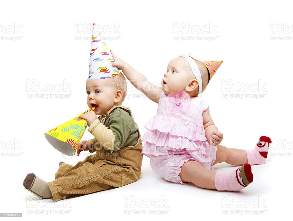Two babies dressed in party hats royalty free stockfoto