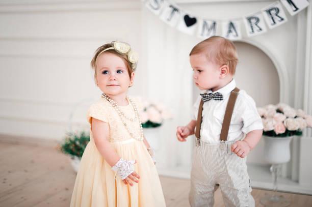 zwei babys hochzeit - junge und mädchen verkleidet als braut und bräutigam - hochzeitsfeier mit kindern stock-fotos und bilder