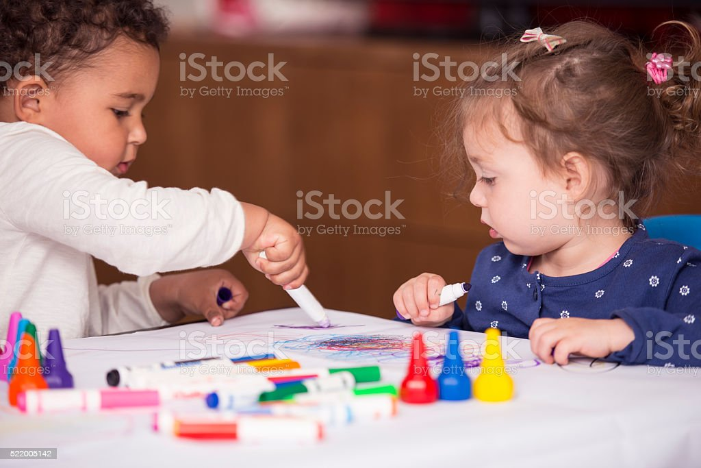 Two baby girls drawing. stock photo