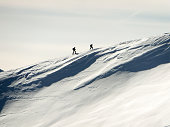 two backcountry skiers hiking up on a long mountain ridge towards the summit near Klosters in the Swiss Alps in deep winter on a great day