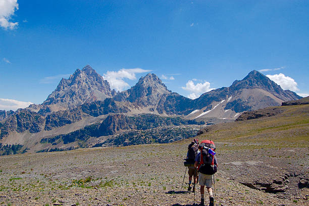 Two Backpackers Approaching Teton Mountains stock photo