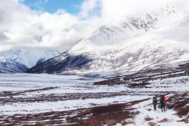 Two backpackers go into the snowy mountains. Altai. stock photo