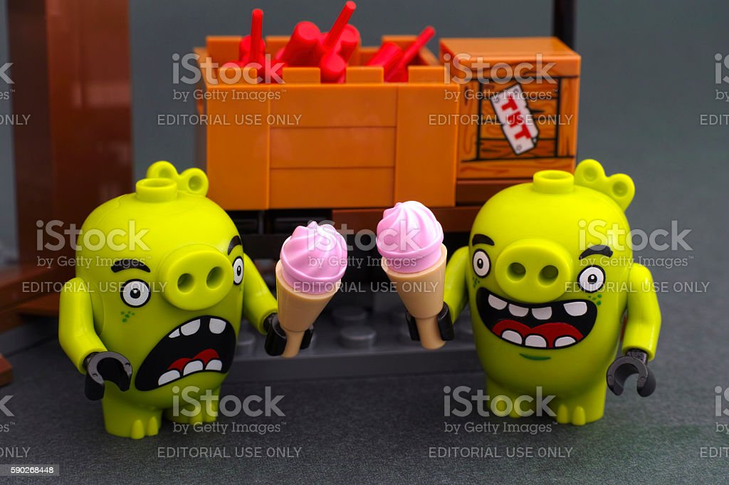 Two bad piggies with ice cream stands near box with dynamite stock photo