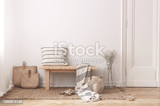 Two bags made of straw next to wooden table with striped pillow and a blanket on it