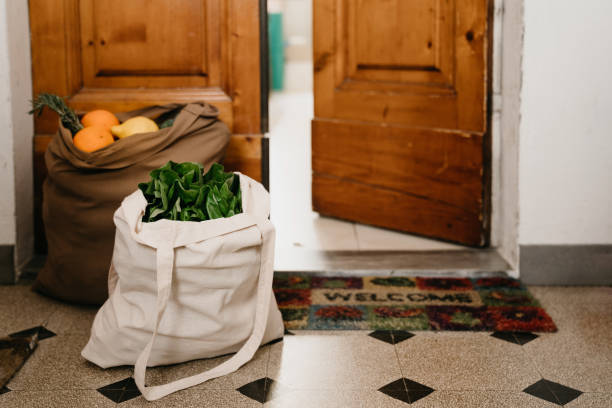 two bags of fruit and vegetables delivered near the home door - grocery home foto e immagini stock