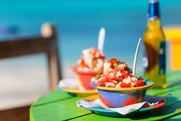 Two Bahamian conch salads on a green table stock photo