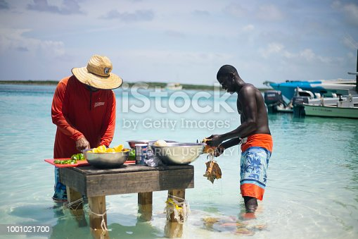 istock Two Bahamian Local/Native Preparing Conch for Conch Salad on a stand in water 1001021700