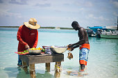 Two Bahamian Local/Native Preparing Conch for Conch Salad on a stand in water