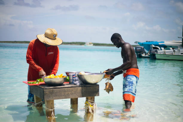 two bahamian local/native preparing conch for conch salad on a stand in water - exuma foto e immagini stock