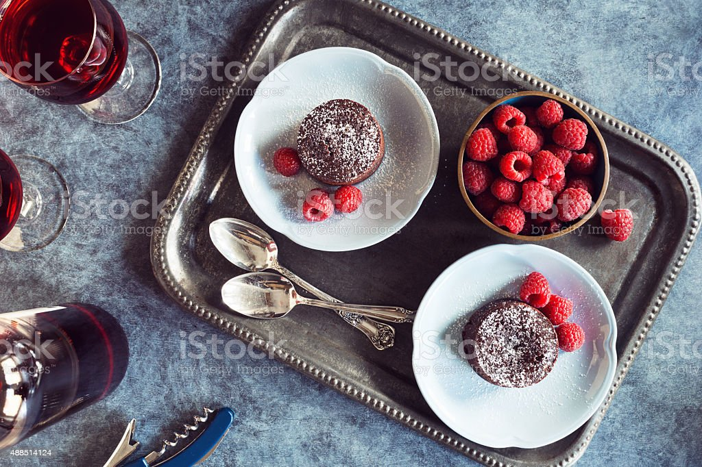 Two Baked Chocolate Lava Cakes with Raspberries and Red Wine stock photo