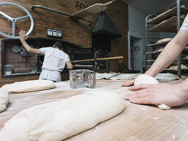 Two bakers kneading a bread dough and cooking bread stock photo