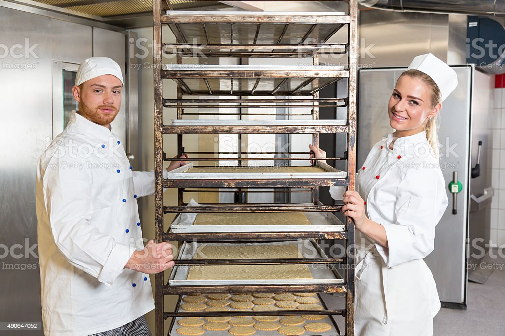 Two bakers posing with shelf containing pastry in bakery stock photo