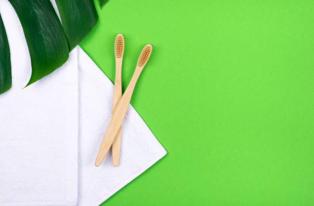 Zwei Bambus-Zahnbürsten auf Handtüchern auf grünem Hintergrund und tropischen Pflanzenblatt monstera . Kunststofffreies Konzept. – Foto