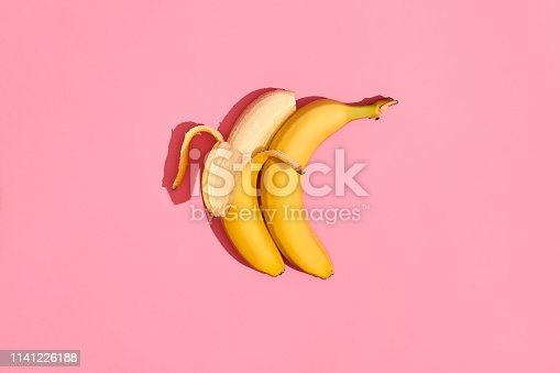 two Banana fresh fruit on pink background couple