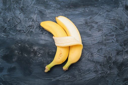 istock Two bananas isolated on dark background. Concept of embracing couple in love and tenderness 1133409284