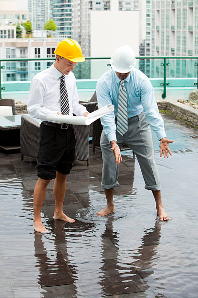 Two barefoot engineers in hard hats looking to fix a leak stock photo
