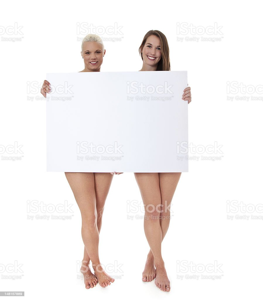 Two barely clothed girls behind blank white sign stock photo