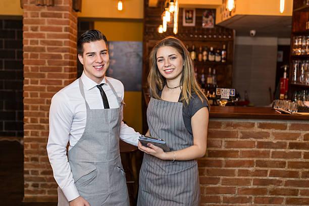 zwei baristas lächelnd in die kamera im café - legere arbeitskleidung stock-fotos und bilder