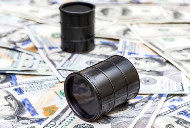 zwei barrel rohöl auf dem hintergrund von dollarnoten. - opec stock-fotos und bilder