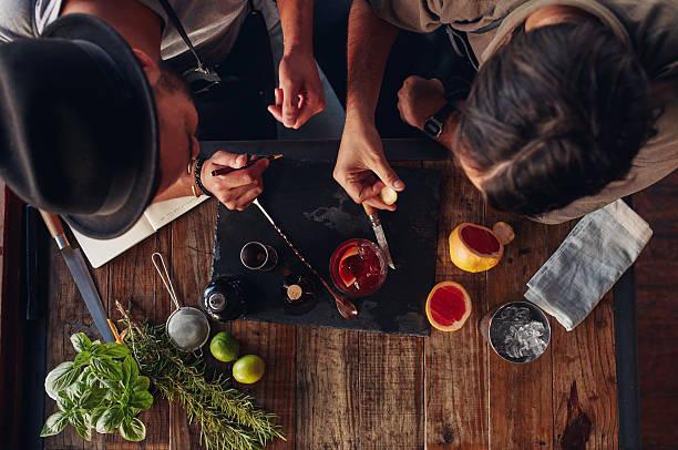 two bartenders discussing creative recipe ideas for cocktails - küche neu gestalten ideen stock-fotos und bilder