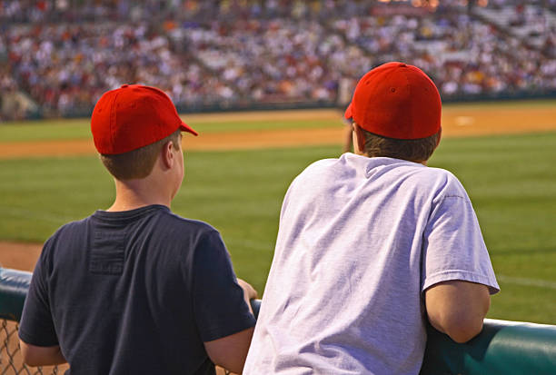 Two baseball fans a the stadium wearing a red cap stock photo