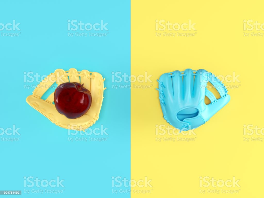 two baseball gloves in different colors , one is holding red apple on pastel background show the concept of catching the fruit. stock photo