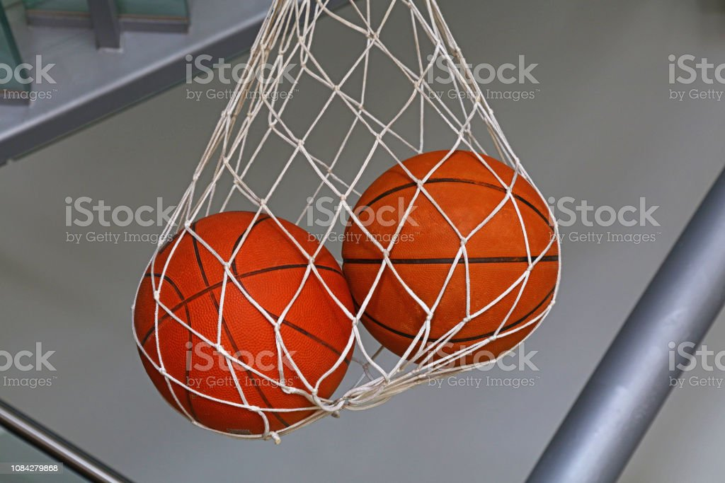 Close up two basketball balls hanging in mesh sack, low angle side...