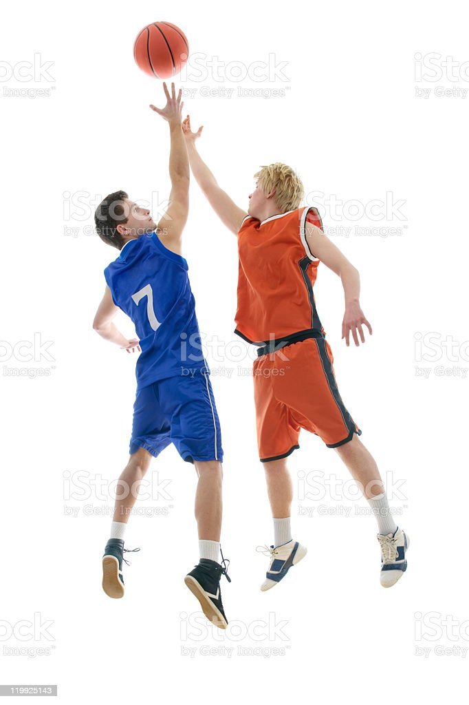 Two basketball player opponents jump to reach for the ball stock photo