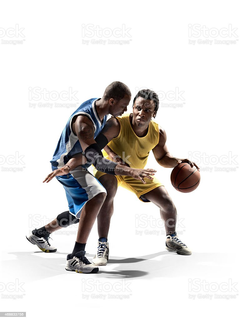 Two basketball players, one in blue, one in yellow uniform stock photo