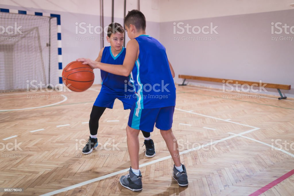 Two basketball players training indoors