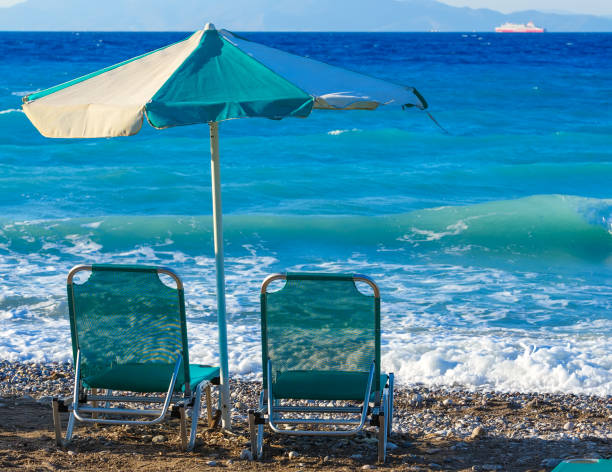 two beach chairs and umbrella on shore of a pebbly beach greece rhodes - dawdle stock pictures, royalty-free photos & images