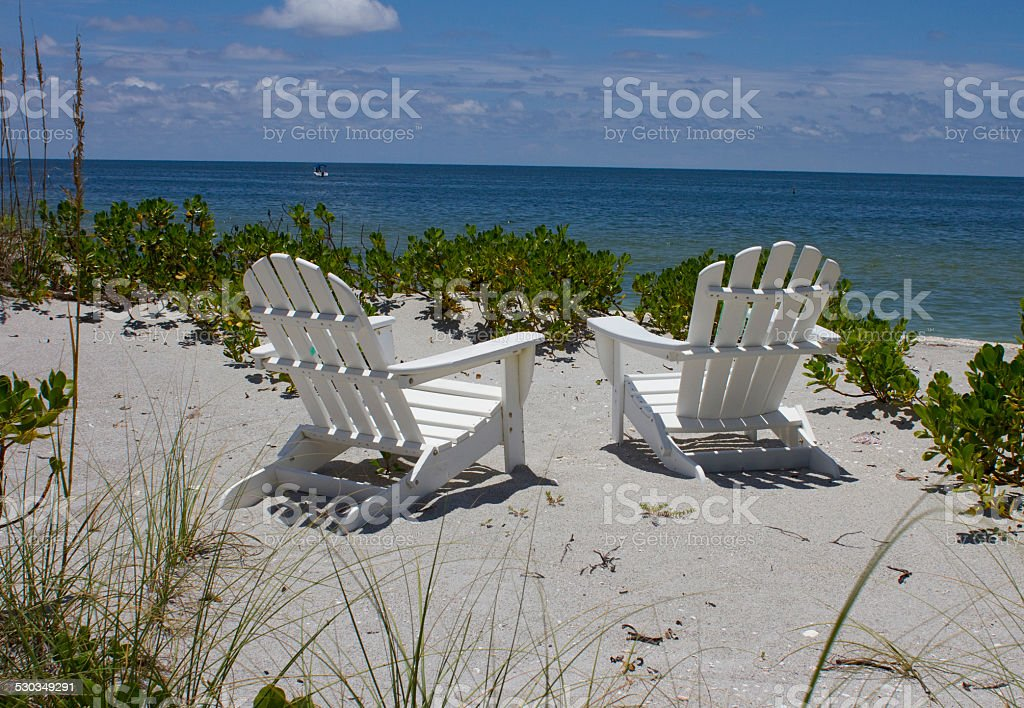 Two beach chairs by the ocean stock photo
