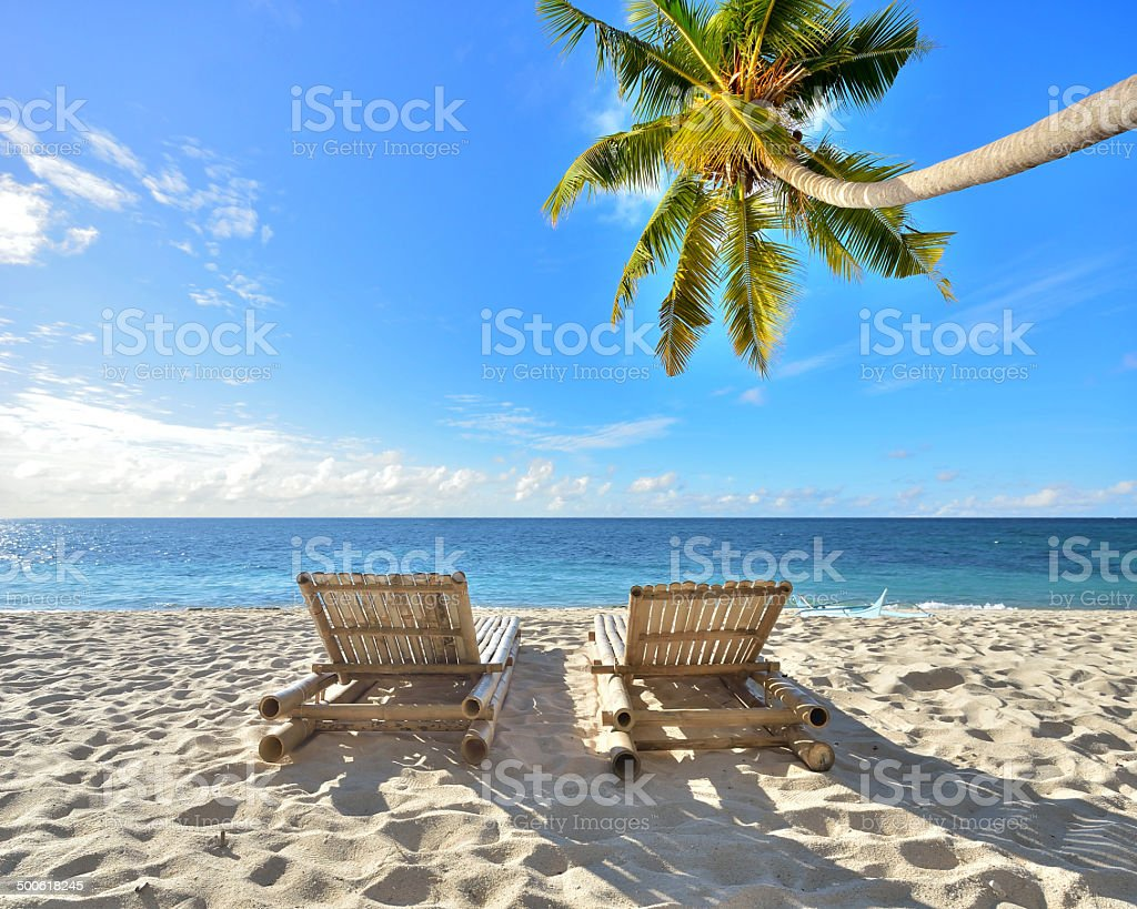 Two beach chairs on idyllic tropical palm beach stock photo