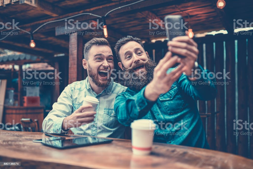 Two Bearded Friends Drinking Coffee and Taking Selfie in Cafe stock photo