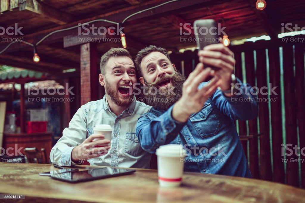 Two Bearded Friends Drinking Coffee and Taking Selfie in Restaurant stock photo