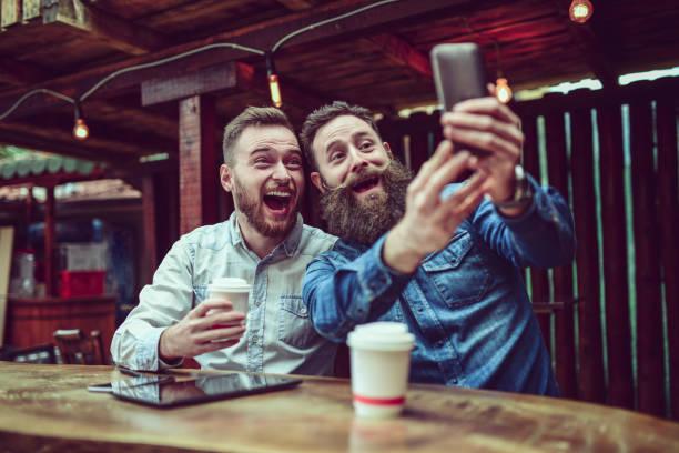 zwei bärtigen freunde, trinken kaffee und nehmen selfie in restaurant - emoticon hug stock-fotos und bilder