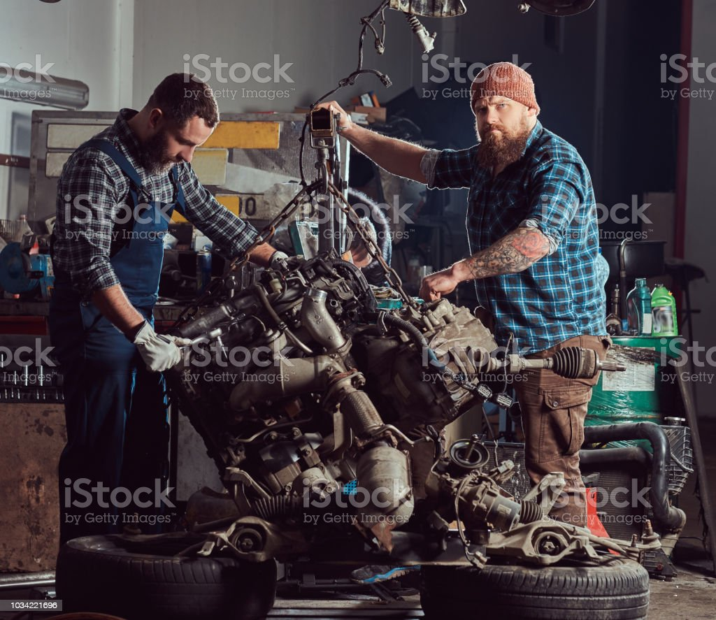 Two Bearded Mechanics Specialist Repairs The Car Engine