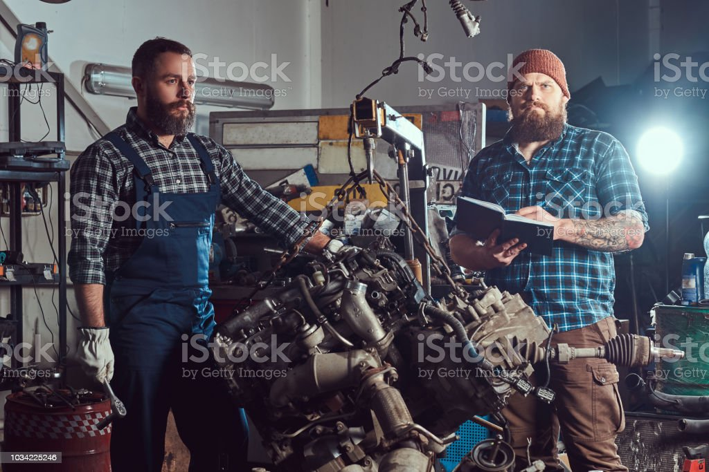 Two bearded mechanics specialist repairs the car engine which is raised on the hydraulic lift in the garage. stock photo