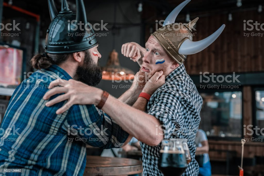 Two bearded men beating each other after watching football match stock photo