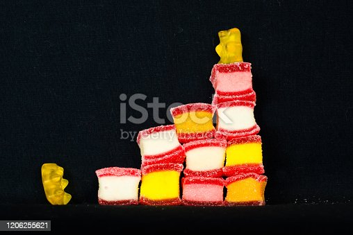 istock Two bears from wine gum are climbing up some colourful candies 1206255621
