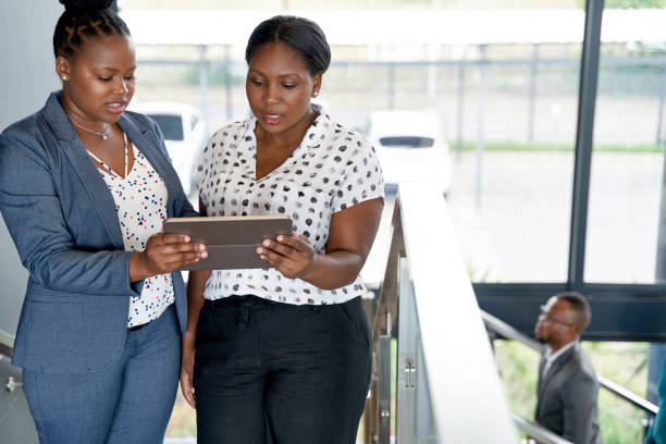 Two beautiful African American businesswomen in bright modern office space working on digital tablet together stock photo