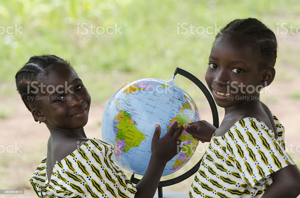 Two Beautiful African Children Pointing to Africa on Globe stock photo