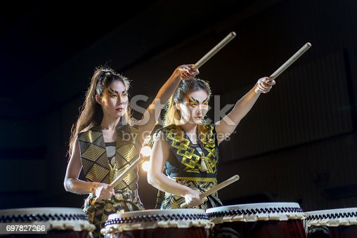 istock two beautiful asian drummer girl with drumsticks, studio concert shot on a dark background. business concept of purposefulness and goal setting 697827266