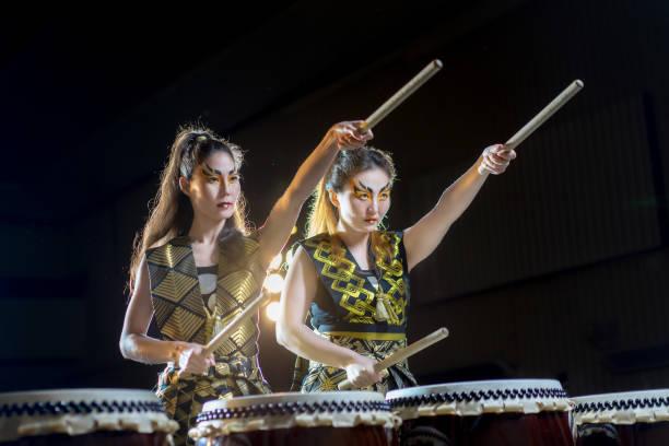menina de duas belas baterista asiático com baquetas, concerto studio atirou-se sobre um fundo escuro. conceito de negócio da determinação e definição de metas - foto de acervo